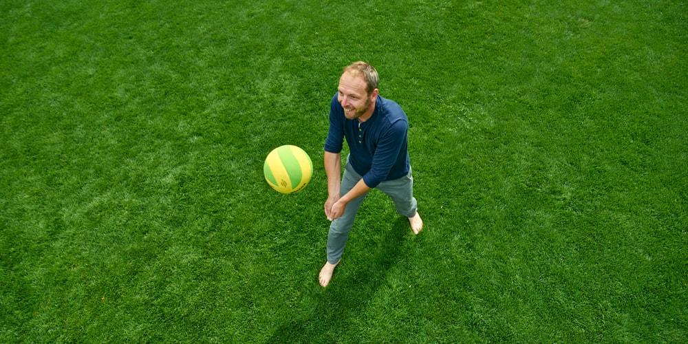 Mann spielt Volleyball im Rasen