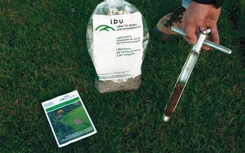 Entnahme einer Bodenprobe im Rasen mit einem speziellen Probenstecher